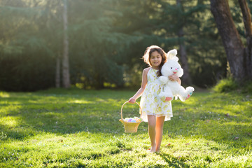 Little girl walking barefoot toward camera, holding Easter basket with eggs and plush toy big bunny