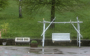 White swings in the garden after the summer rain.