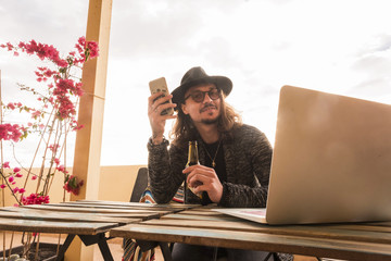 young hipster use phone and laptop outdoor