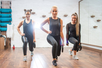 Three young sporty women exercising with weights at gym.