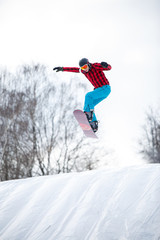 Image of athlete in helmet riding snowboard from snow slope