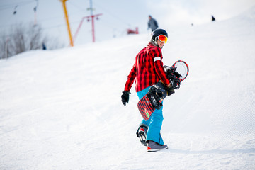 Photo from back of athlete walking with snowboard