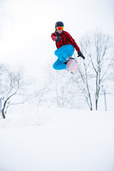 Image of sporty man with snowboard jumping in snowy resort
