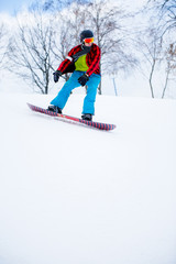 Photo of athlete in plaid shirt with snowboard riding in snowy resort