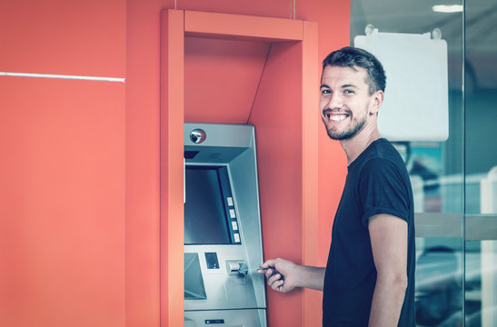 Young smiling man using ATM machine