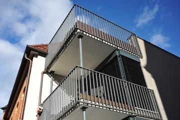 Moderner Balkon mit Metall-Geländer an Neubau-Hausfront