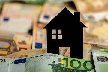A black paper house with euro banknotes in background