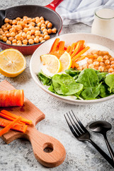 Modern vegan food, savory yogurt bowl with beans, chickpeas, spinach, spicy carrots, lemon, Gray stone background, copy space