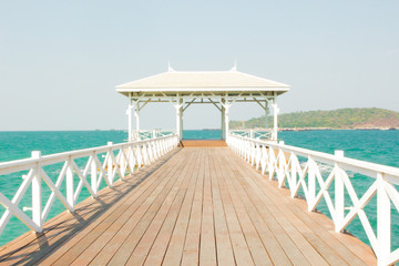 Wooden walk way to white pavilion on the sea
