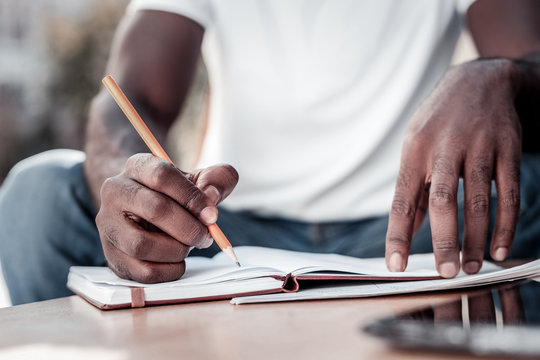 Preparation process. Scaled up look on hands of a young man holding a pencil and writing down some necessary information while sitting outdoors.