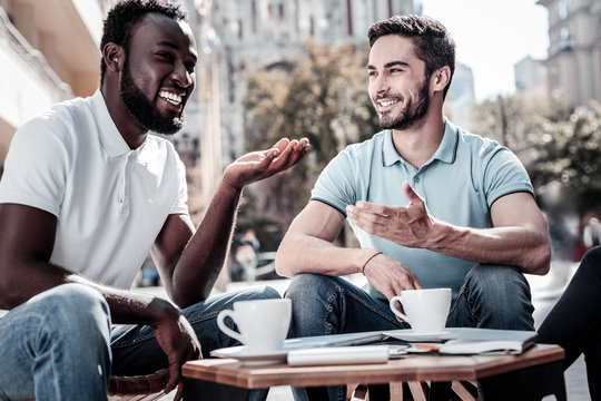 We love what we do. Happy coworkers gesturing and smiling cheerfully while enjoying a pleasant conversation outdoors.