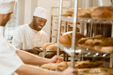 handsome bakers working together at baking manufacture