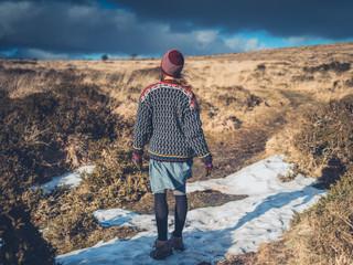 Woman walking in melting snow on moor