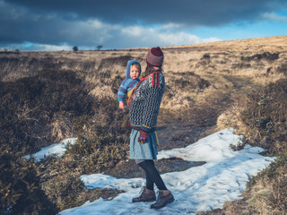 Young mother with baby on moor with snow