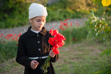 sad beautiful little girl in hat and coat with poppies bouquet in one hand in springtime sunset