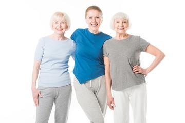 Portrait of three smiling sportswomen isolated on white