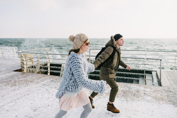 young couple holding hands and running on winter quay