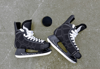 Pair of hockey skates with puck on a ice rink.