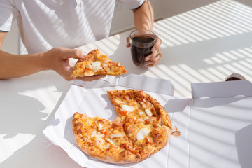 close up man hand eating pizza while working in laptop computer