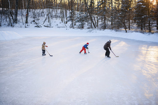 Father playing ice-hockey with his two sons