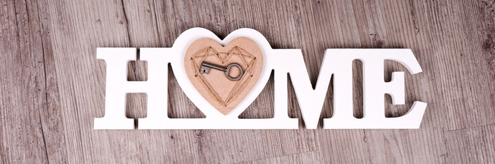 The key in the heart on the word Home in front of wooden background