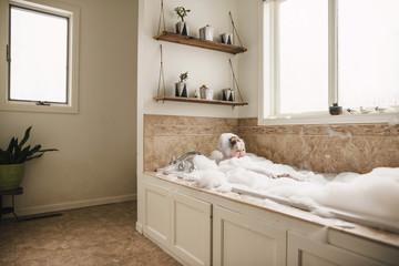 Boy sitting in a bubble bath laughing