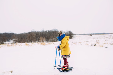 Girl snowshoeing in rural winter landscape