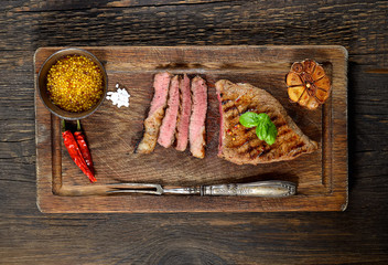 Steak with herbs  on a wooden background