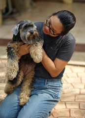 Asia woman with glasses and casual wear clothes with her small black fluffy dog
