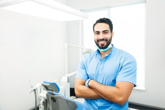 Portrait of hadsome dentist doctor wears blue uniform, indoor shot in modern dentist office