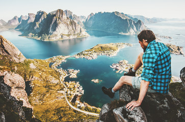 Travel Man sitting on cliff edge in Norway lifestyle adventure outdoor summer vacations Reinebringen mountain enjoying aerial view Lofoten islands