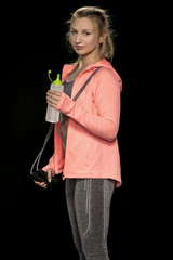 beautiful athletic girl is practicing with a skipping rope, isolated on the black background