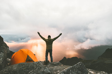 Man traveler happy raised hands on mountain top near of tent camping outdoor Travel adventure lifestyle success concept hiking active vacations enjoying sunset view