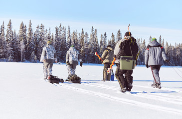 Winter fisherman's hiking on lake ice