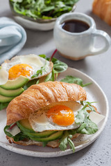 Breakfast with Croissant sandwiches with Fried Egg, Salad Leaves and avocado