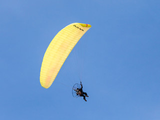 Foto op Aluminium Luchtsport The sportsman on a color motorized parachute flies in the clear day in the sky above Caesarea in Israel