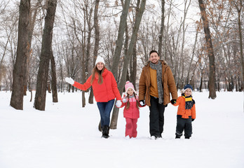 Happy family walking in snowy park on winter vacation