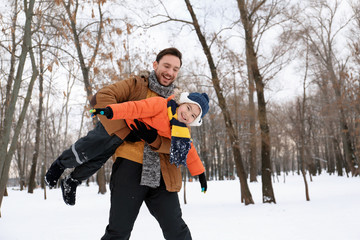 Happy father with son playing in snowy park on winter vacation