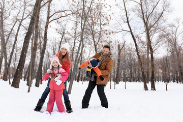 Happy family playing in snowy park on winter vacation