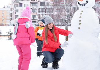 Happy family making snowman in park on winter vacation