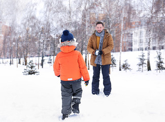 Happy man with son playing in snowy park on winter vacation