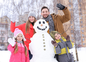 Happy family with snowman in park on winter vacation