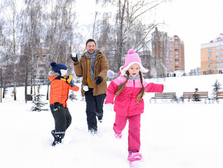 Happy man with children playing in snowy park on winter vacation