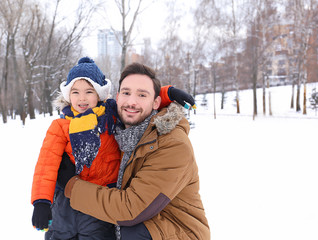 Happy man with son in snowy park on winter vacation