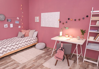 Comfortable bed and desk in modern children room