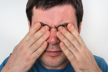 Man with eyes pain is holding his aching eyes