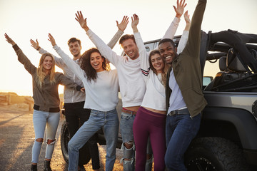 Young adult friends with hands in the air standing by jeep, close up
