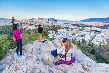 Tourist people on viewpoint sightseeing on lovely ancient Parthenon in Athens. Day scenery.