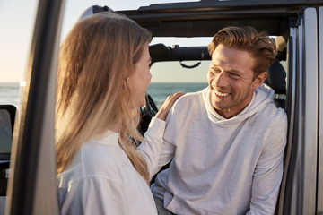 Young couple looking at each other by car, close up