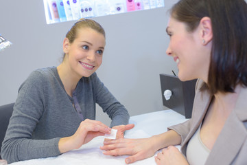 attractive nail salon worker giving a manicure to customers